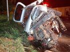 Carro bate em caminhão estacionado, capota e motorista fica preso às ferragens