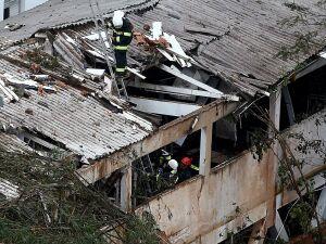 Bombeiro no telhado de casa, onde o jato que levava o presidenciável Eduardo Campos, cai, em Santos (SP). tCampos, que era candidato pelo PSB à presidência da República, morreu em um desastre aéreo, o avião em que estava caiu em uma área residencial de Sa