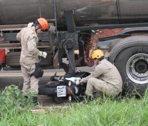 Motocicleta ficou presa embaixo do caminhão tanque