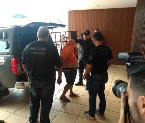 Policiais civis levam homem detido na operação Luz da Infância 3 a delegacia em Campo Grande