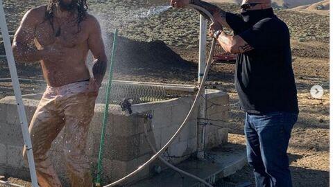 Jason Momoa toma banho de mangueira após ficar coberto de lama