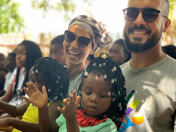 Taina e Renato com criança em aldeia africana
