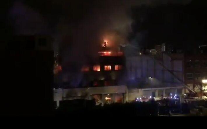 Jovem perto de saltar do prédio em chama