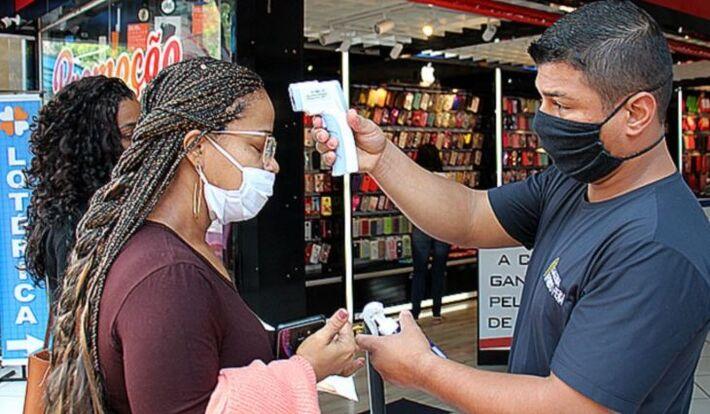 Pessoa recebendo testagem de calor em frente a comercio na Capital