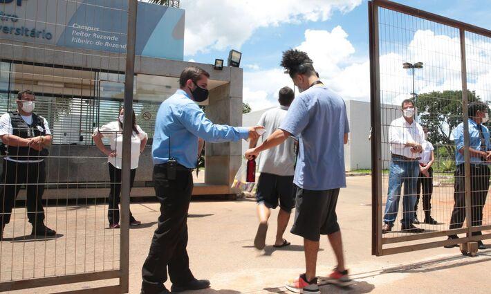 Jovens entram pelos portões de universidade para realizar a versão impressa da prova, aplicada na semana passada