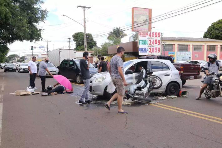 Garupa da moto foi parar na altura da janela do veículo. Motoqueiro, debaixo de guarda-sol, é atendido por quem passava pelo local
