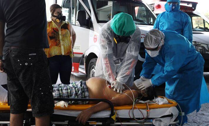 Médicos do Serviço de Resgate de Emergência (SAMU) tentam reanimar um paciente com suspeita de COVID-19, em Manaus