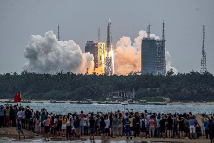 Pessoas assistem ao lançamento do foguete Long March 5B no Centro de Lançamentos de Wencha em 29 de abril.