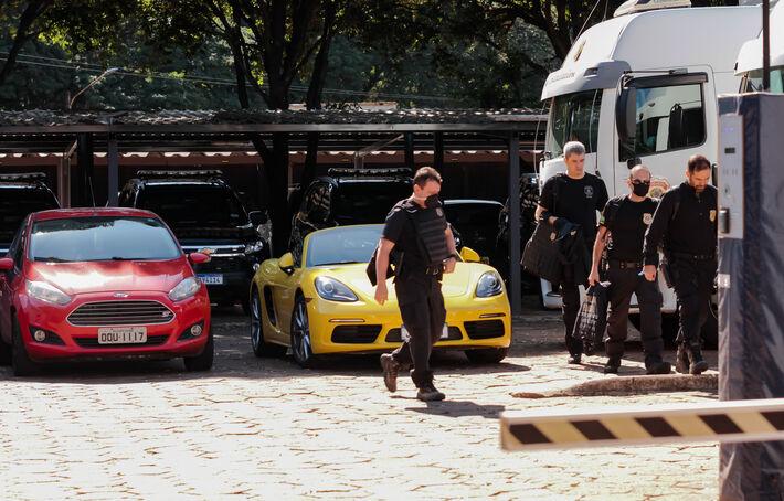 Equipe da Polícia Federal ao final dos trabalho passam próximo aos veículos apreendidos.