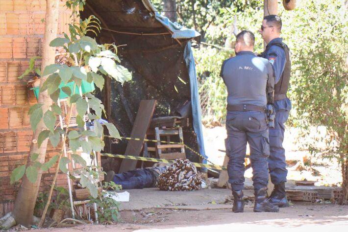 Policiais militares conversam em frente ao corpo, no chão de varanda da chácara. Foto: Henrique Kawaminami, fotojornalista do site CAMPO GRANDE NEWS
