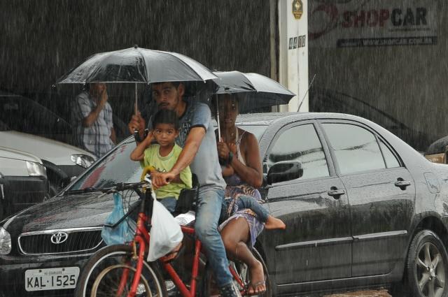 Família trafega pelo Centro protegidos por guarda-chuvas<br />Foto: Ademir Almeida