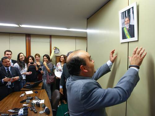 O deputado Bernardo Santana (PR/MG) coloca retrato do ex-presidente Lula na parede do escritório da liderança do partido durante entrevista coletiva.<br />Foto: André Coelho / Agência O Globo