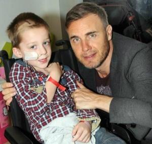 """Um menino britânico de quatro anos que foi diagnosticado com um tumor no cérebro morreu na terça-feira após conseguir realizar sua lista de desejos.</p> <p style=""""text-align: justify;"""">Em fevereiro, ele recebeu a visita de Gary Barlow, vocalista do grupo"""
