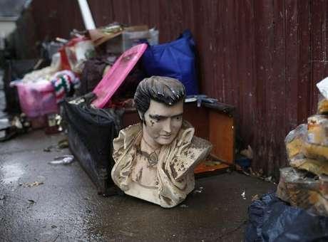 Busto de Elvis Presley é deixado na calçada com destroços resultantes da passagem do furacão Sandy no bairro de Midland Beach, em Staten Island, na cidade de Nova York. 13/11/2012