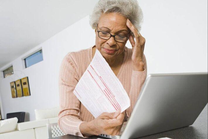 Mulher faz contas de dívidas