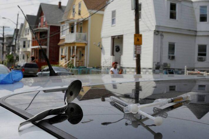 Seringa com heroína e uma colher são fotografadas em cima de um carro em Lynn, Massachusetts: jovem de 20 anos morreu por overdose nesse local