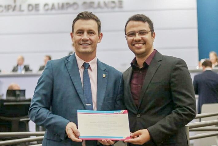 Professor Thiago Müller da Silva (lado direito) recebeu moção de congratulação das mãos do vereador André Salineiro