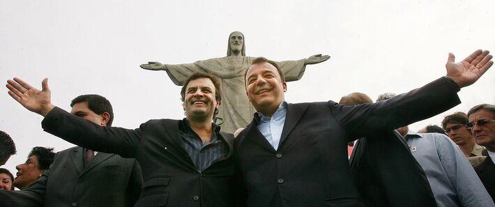 """Os governadores Aécio Neves (Minas Gerais) e Sérgio Cabral Filho (Rio de Janeiro), à direita, posam em frente à estátua do Cristo Redentor para estimular a candidatura da estátua ao concurso das """"Sete Novas Maravilhas do Mundo"""", no Rio de Janeiro (RJ)"""