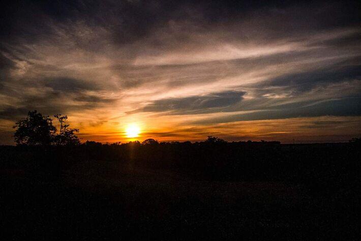 Sol nasce entre nuvens