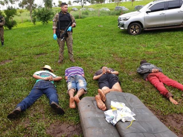Policial paraguaio vigia quatro presos em local do confronto, nesta manhã