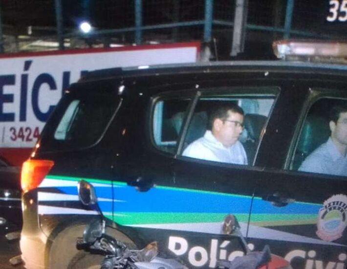 Pedro Pepa desce da viatura da Polícia Civil ao chegar em delegacia depois de ser preso na sessão da Câmara