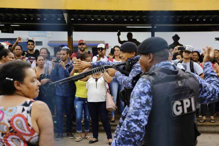 Guarda Municipal apontando arma para manifestantes. (
