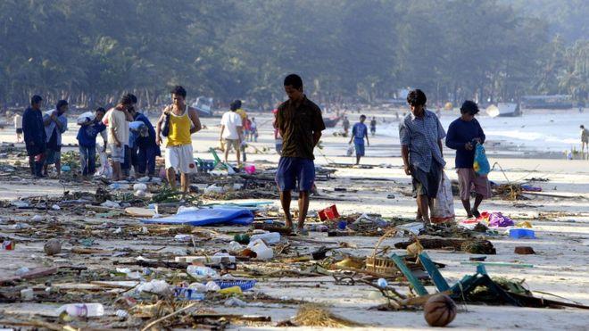 Sobreviventes andam pelos escombros da praia de Patong, em Phuket, no dia seguinte ao tsunami