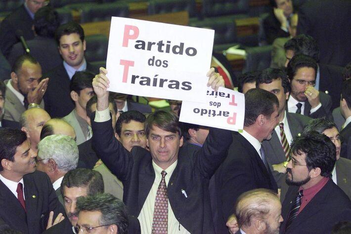 """Em 2003, o deputado federal Jair Bolsonaro segura um cartaz com a expressão """"Partido dos Traíras"""", em alusão ao PT, no plenário da Câmara dos Deputados -"""