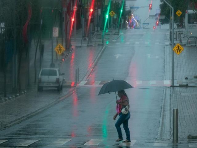 Chuva e tempo escuro teimando em deixar dia amanhecer fizeram neon com as luzes da Rua 14 de Julho
