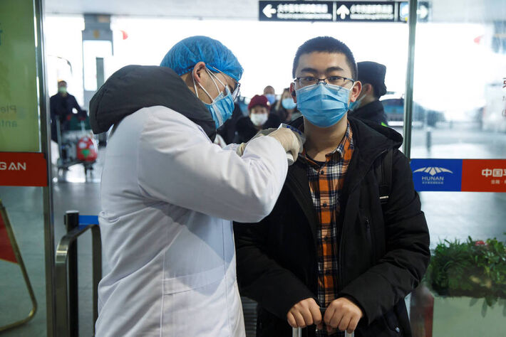 Médico mede temperatura de um homem no aeroporto de Changsha, na província de Hunan, na China