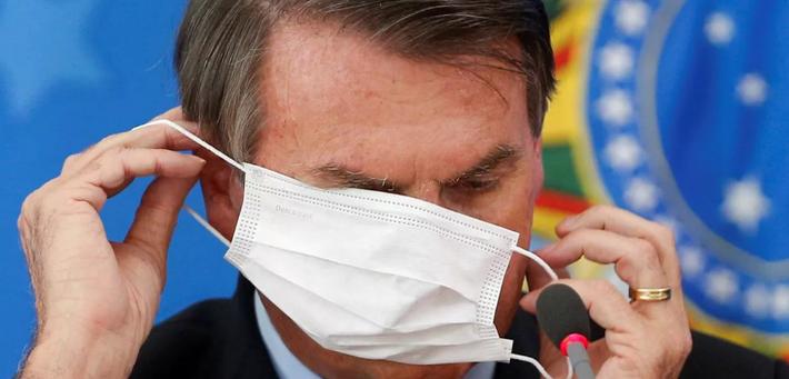 Presidente tantando colocar máscara em coletiva