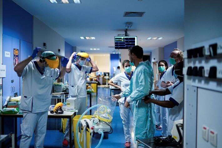 Funcionários de hospital Erasme, em Bruxelas, na Bélgica, colocam roupas de proteção para trabalhar com pacientes infectados pelo novo coronavírus. Imagem de 27 de março de 2020