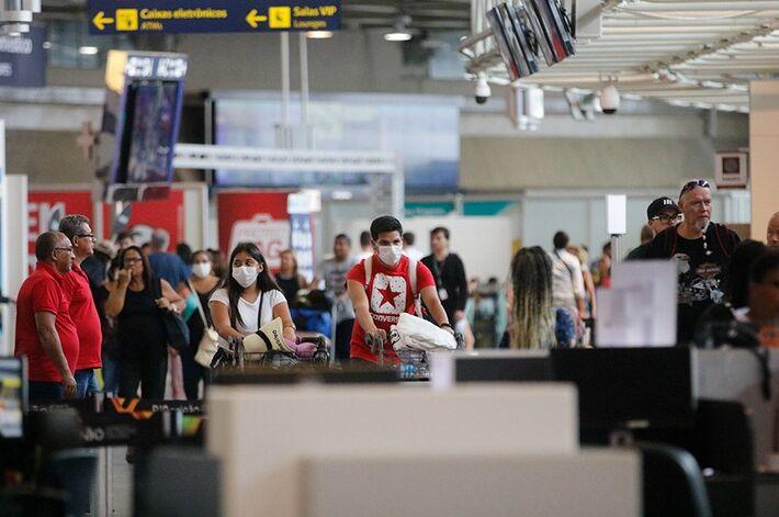 Pessoas de máscara em aeroporto brasileiro: resposta à crise precisará de gastos urgentes e não previstos. Presidentes da Câmara e do Senado já sinalizaram que apoiam a medida