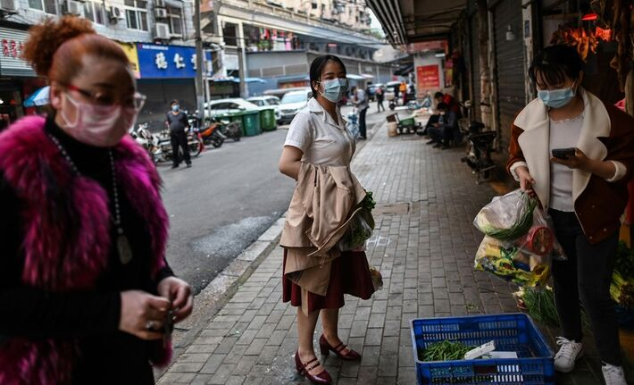Usando máscaras, mulheres fazem compras em Wuhan, após o fim da quarentena na província de Hubei, na China, na quarta-feira (8.abril)