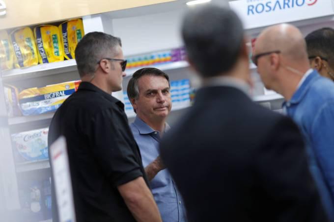 O presidente Jair Bolsonaro tira foto com simpatizante durante saída no Distrito Federal