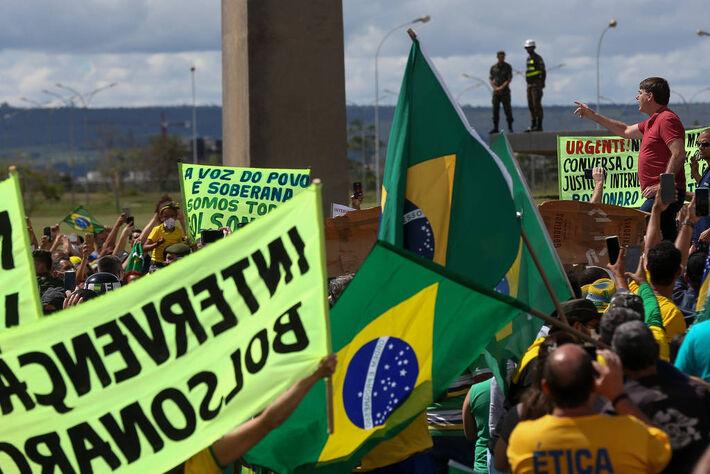 O presidente Jair Bolsonaro discursa diante do QG do Exército, em Brasília, para apoiadores que participavam de uma carreata pró-governo e contra as medidas de isolamento contra o coronavírus, neste domingo (19)