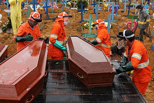 Caixões sendo descarregados para serem enterrados em uma vala comum no cemitério de Nossa Senhora em Manaus, estado da Amazônia, Brasil, em 6 de maio de 2020