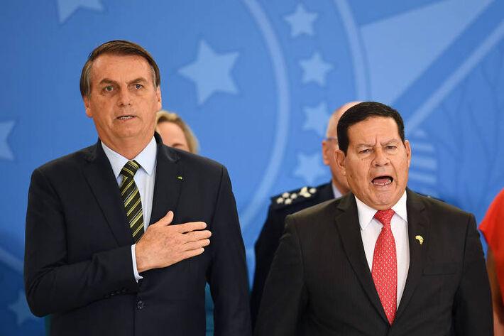 O presidente brasileiro, Jair Bolsonaro, e o vice, Hamilton Mourão, cantam o hino nacional durante cerimônia no Palácio do Planalto