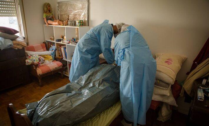 Socorristas do Samu preparam cadáver de um mulher idosa que morreu com suspeita de Covid-19