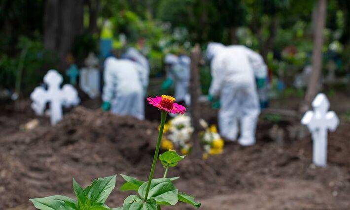 Coveiros trabalham no cemitério municipal de Santa Tecla, vestindo roupas de biossegurança em 22 de junho de 2020, em Santa Tecla, El Salvador. O governo acaba de inaugurar um hospital exclusivo para pacientes com COVID-19. O país enfrenta ainda curva asc