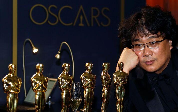 Bong Joon-Ho admira as estatuetas que ganhou no Oscar 2020