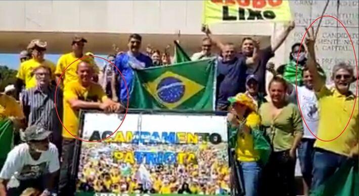 """Renan Santos apoiado na placa com dizeres do """"Acampamento Patriota"""" e Elano Almeida fazendo o gesto de """"V"""" com os dedos"""
