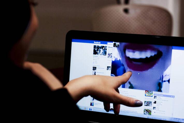 Usuária assiste a vídeo no Facebook, pelo computador. Ela aponta para a tela, que mostra a página da rede social com um vídeo em que aparece a boca de uma mulher Usuária assiste a vídeo no Facebook, pelo computador. Ela aponta para a tela, que mostra a pá