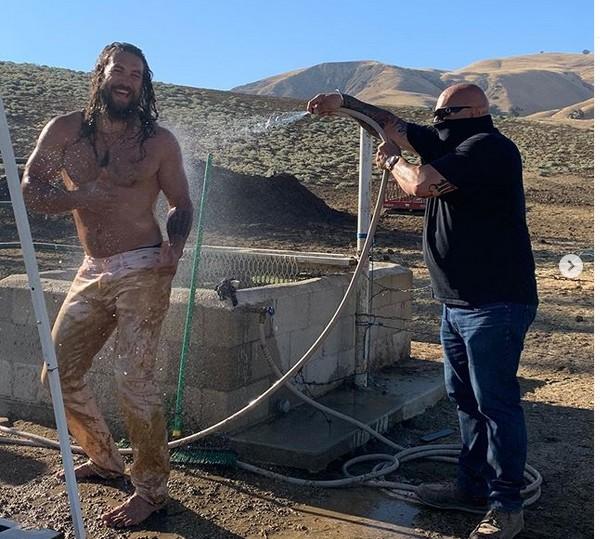 O ator Jason Momoa tomando banho de mangueira após um passeio de bugue