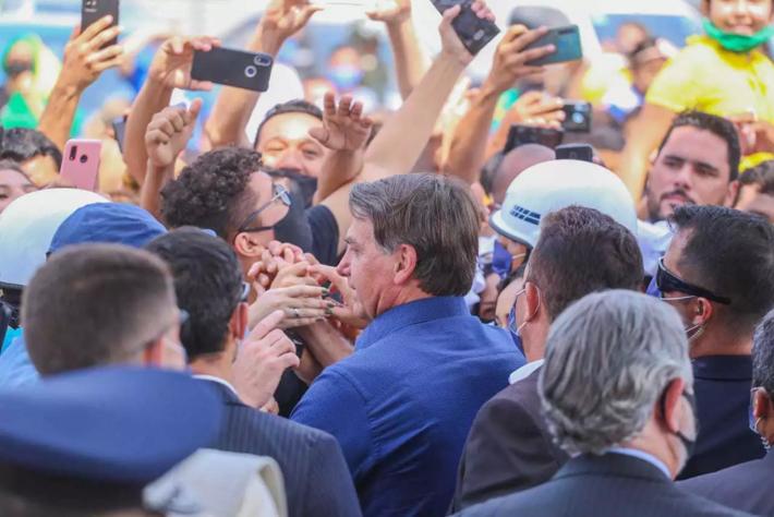 Jair Bolsonaro cumprimenta fãs espremidos na grade do cercadinho