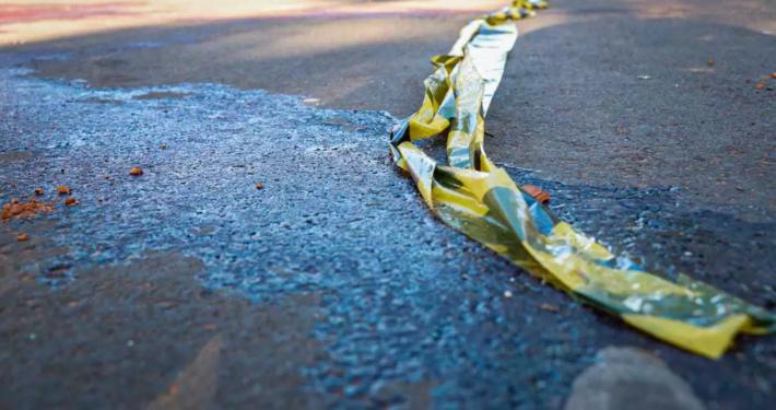 Manchas de sangue no asfalto na rua onde Osvando Batista Lemes, 34 anos, foi morto