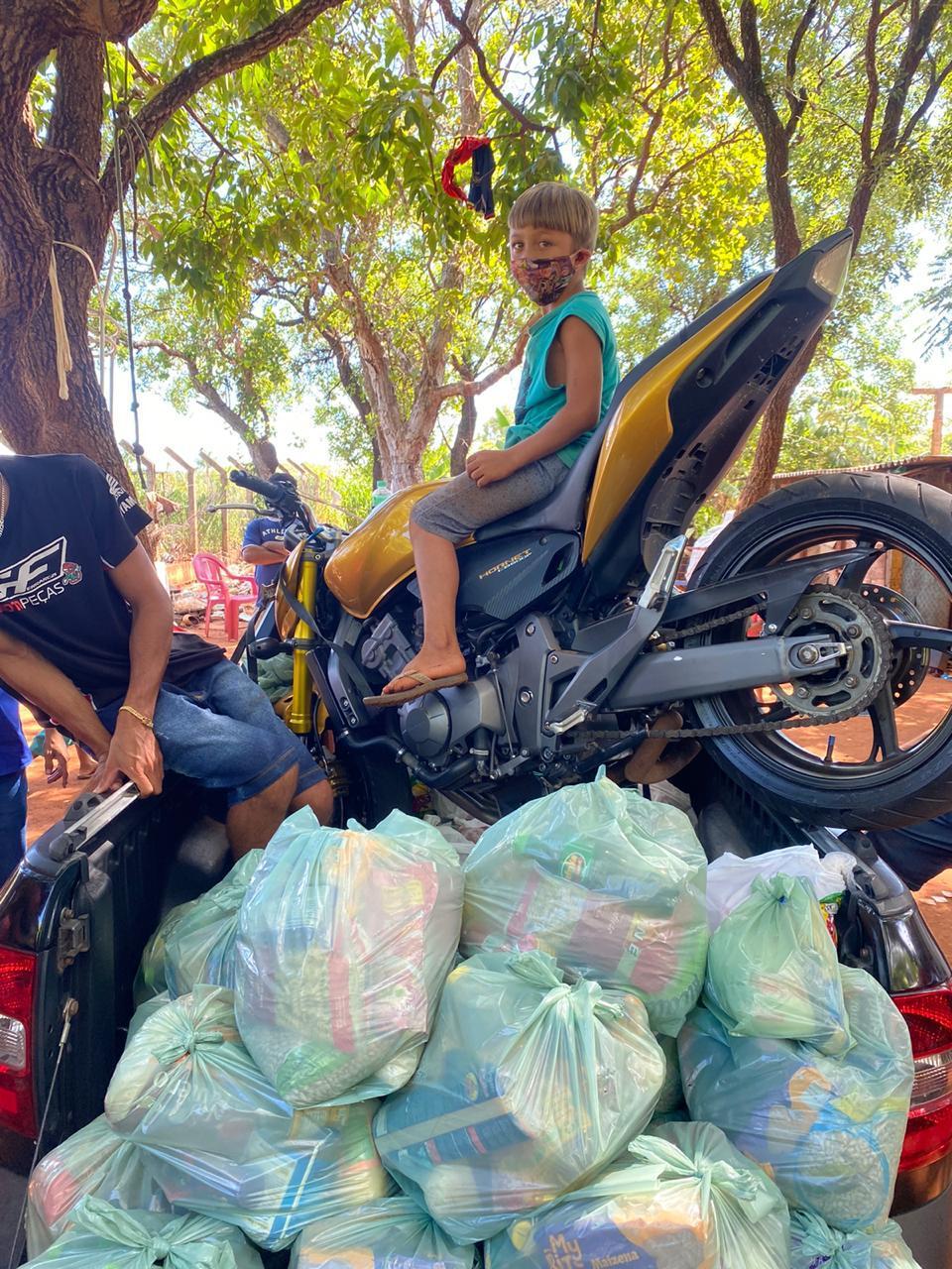 Criança sobre moto durante entrega de alimentos
